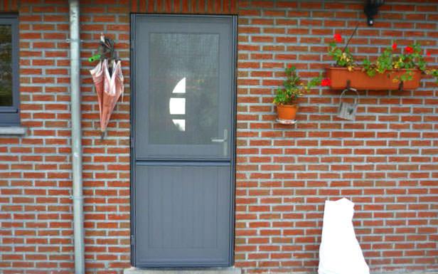 Porte PVC Renolit Gris Anthracite RAL 7016 avec panneau planchettes dans l'allège et vitrage au-dessus. Devant la porte, une porte moustiquaire